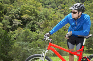 Male cyclist leaning on mountain bikeの写真素材 [FYI02940721]