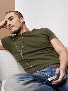 Man listening to MP3 player on sofaの写真素材 [FYI02940745]
