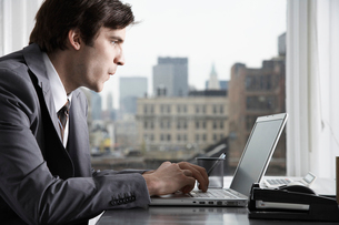 Businessman typing with laptop in officeの写真素材 [FYI02940749]
