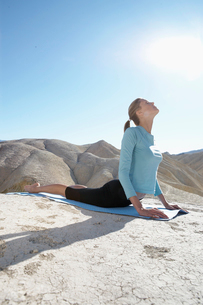 Young woman stretching in desertの写真素材 [FYI02940754]