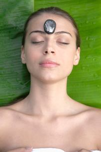 Young woman receiving hot stone therapyの写真素材 [FYI02940782]