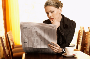 Woman reading newspaper in cafeの写真素材 [FYI02940888]