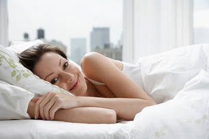 Portrait of mid adult woman in bedの写真素材 [FYI02940893]