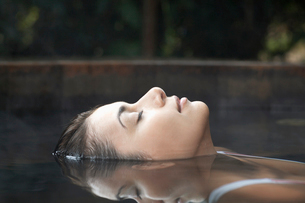 Young woman floating in hot tubの写真素材 [FYI02940894]