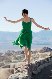 Woman in dress walking on stone wallの写真素材 [FYI02940911]