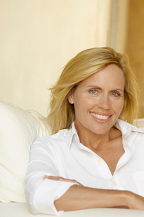 Mature woman in white shirt on armchairの写真素材 [FYI02940931]