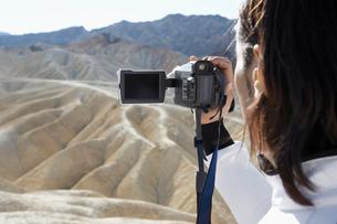 Man using video camera in desertの写真素材 [FYI02940939]