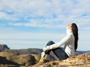 Young woman sitting on rocky hillの写真素材 [FYI02941036]
