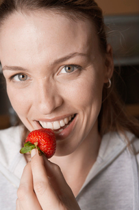Young woman eating strawberryの写真素材 [FYI02941038]