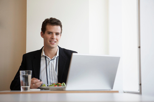 Businessman with laptop eating saladの写真素材 [FYI02941041]