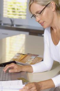 Mature woman booking travel via internetの写真素材 [FYI02941050]