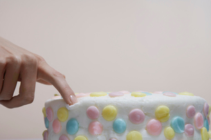 Close-up of womans finger on cakeの写真素材 [FYI02941067]
