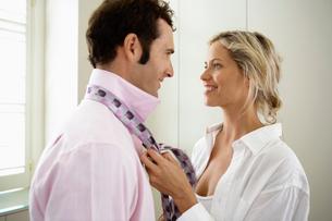 Woman tying necktie for husbandの写真素材 [FYI02941072]