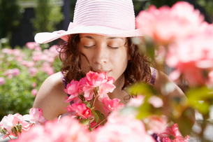 Young woman smelling flowersの写真素材 [FYI02941115]
