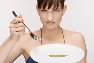 Mid adult woman eating single mangetoutの写真素材 [FYI02941141]