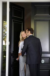 Husband kissing wife at front doorの写真素材 [FYI02941146]