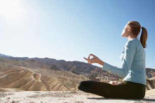 Young woman in lotus position in desertの写真素材 [FYI02941156]