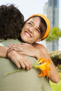 Couple hugging, woman holding flowerの写真素材 [FYI02941158]