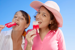 Two young women eating ice lolliesの写真素材 [FYI02941177]
