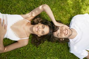 Young couple lying on lawnの写真素材 [FYI02941223]