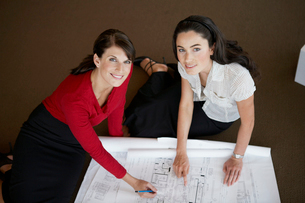 Two businesswomen examining blueprintsの写真素材 [FYI02941250]