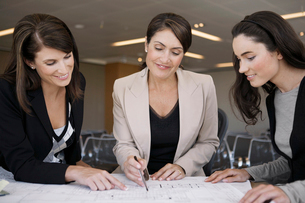 Three businesswomen examining blueprintの写真素材 [FYI02941257]