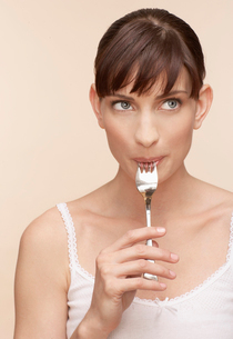 Mid adult woman with fork in mouthの写真素材 [FYI02941259]