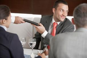 Businessman taking menu at dining tableの写真素材 [FYI02941270]