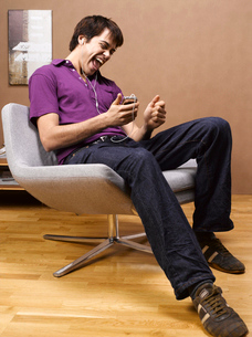 Man listening to music on armchairの写真素材 [FYI02941294]
