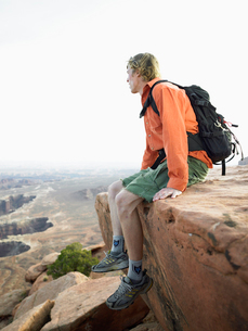 Male hiker sitting on cliffの写真素材 [FYI02941327]