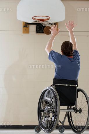 Wheelchair-bound man shooting basketの写真素材 [FYI02941352]