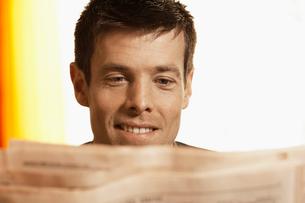 Mid adult man reading paperの写真素材 [FYI02941400]