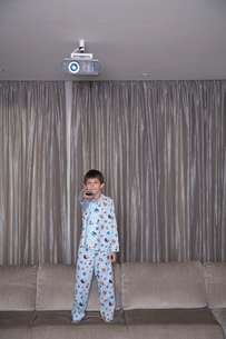 Boy standing and using remote controlの写真素材 [FYI02941424]