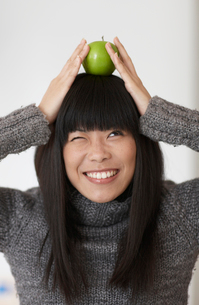 Woman Balancing Single Apple on Headの写真素材 [FYI02941489]