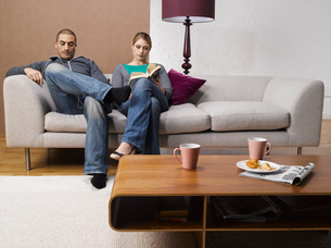Couple reading and listening to musicの写真素材 [FYI02941492]