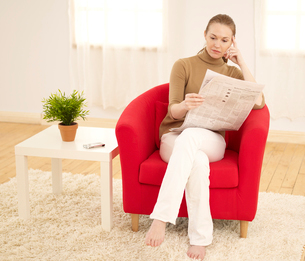 Woman Reading Newspaper in Living Roomの写真素材 [FYI02941520]