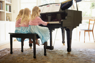 Triplets playing piano in living roomの写真素材 [FYI02941556]