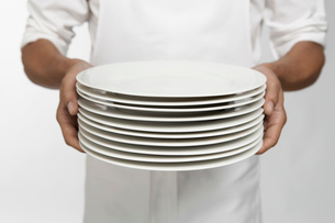 Chef holding stack of dinner platesの写真素材 [FYI02941565]