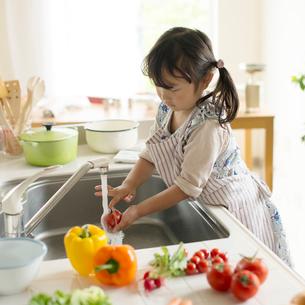 キッチンで野菜を洗う女の子の写真素材 [FYI02941592]