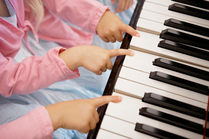 Triplets playing piano (focus on hands)の写真素材 [FYI02941637]