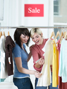 Women Looking at Price Tag of T-Shirtの写真素材 [FYI02941658]