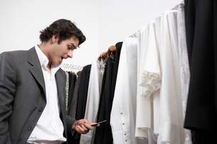 Man text messaging in clothing storeの写真素材 [FYI02941748]