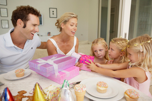 Parents giving presents to tripletsの写真素材 [FYI02941761]