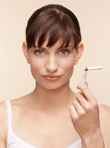 Mid adult woman holding broken cigaretteの写真素材 [FYI02941764]