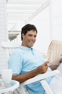 Man reading newspaper on lounge chairの写真素材 [FYI02941792]