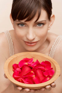 Mid adult woman holding bowl of petalsの写真素材 [FYI02941793]