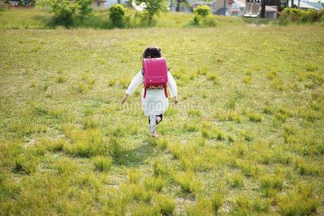 公園を走るランドセルを背負った女の子の写真素材 [FYI02941817]