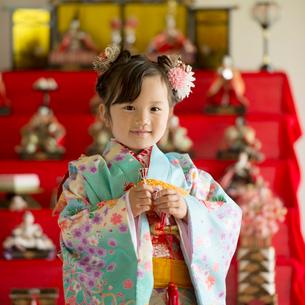 雛人形の前で微笑む女の子の写真素材 [FYI02941819]