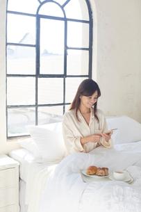 広いベッドルームで携帯を見ながら朝食を食べる女性の写真素材 [FYI02941842]