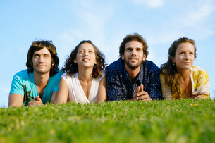 Four people lying on lawn and looking upの写真素材 [FYI02941846]